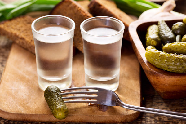 Two shots of Polish vodka served with pickles