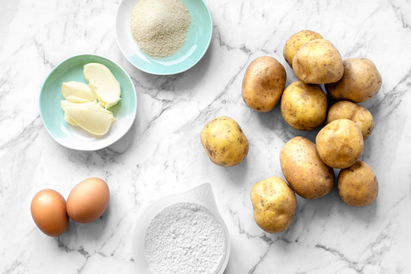 Top view of ingredients for kopytka - Polish Potato Dumplings: Potatoes, Flour, Eggs, and butter with breadcrumbs for a tasty topping.