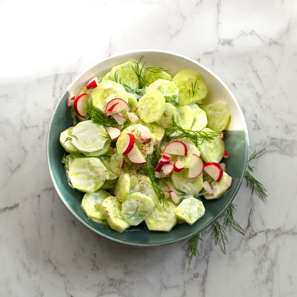 "Polish Cucumber salad with cream and radishes - ""mizeria"" on a marble table, view from the top"