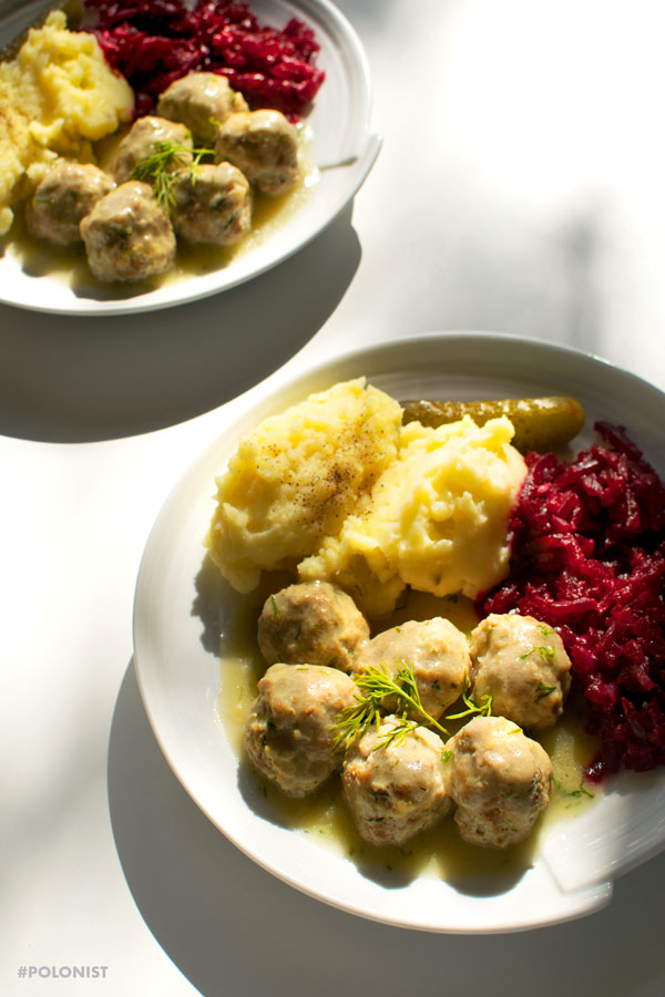 Polish meatballs (Pulpety0 in dill sauce, served with mash potatoes and beetroot salad on a white plate, on a white background. Two plates.
