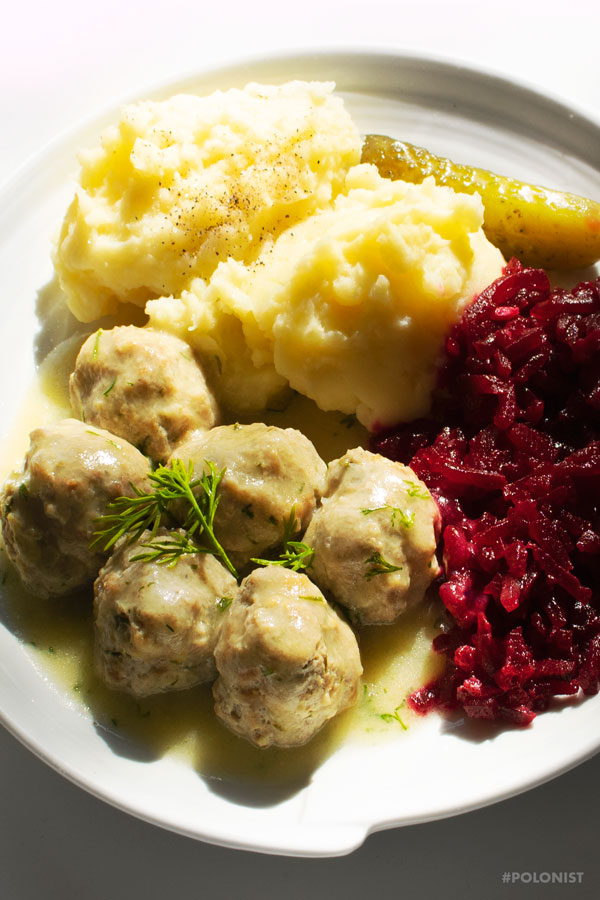 Polish meatballs (Pulpety0 in dill sauce, served with mash potatoes and beetroot salad on a white plate, on a white background. Close-up.