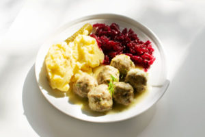 Polish meatballs (Pulpety0 in dill sauce, served with mash potatoes and beetroot salad on a white plate, on a white background. Horizontal image.