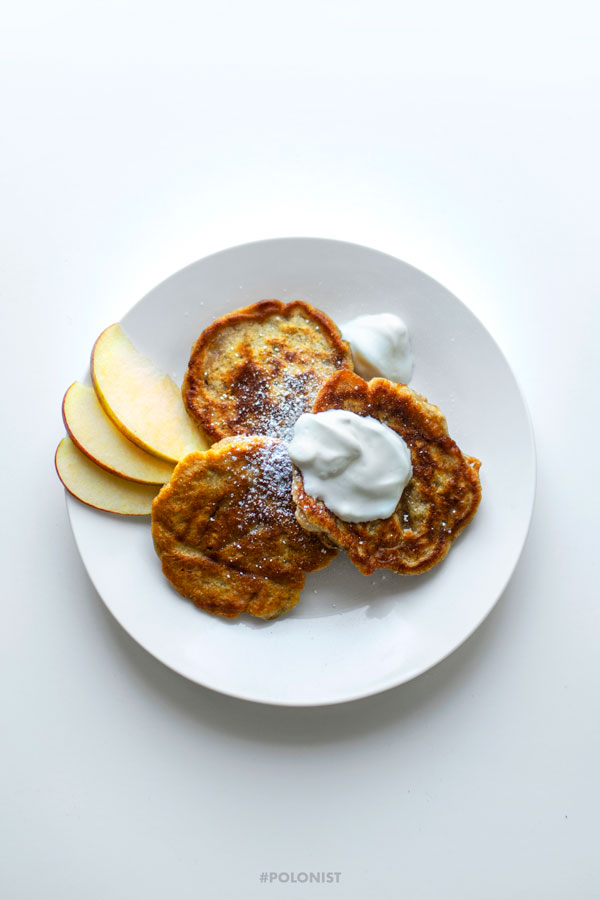 Polish apple pancakes - Racuchy z jabłkami - served on a white plate, topped with cream, powdered sugar and apple slices. Top view image.