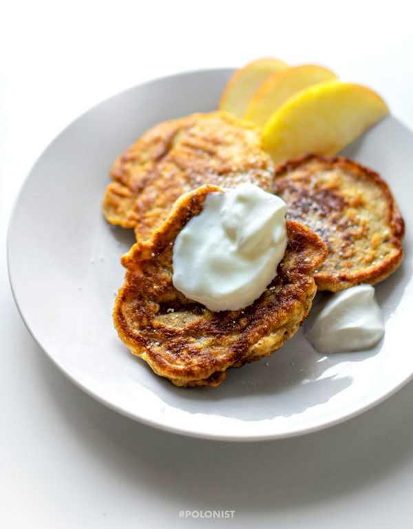 Polish apple pancakes - Racuchy z jabłkami - served on a white plate, topped with cream, powdered sugar and apple slices. Vertical image.