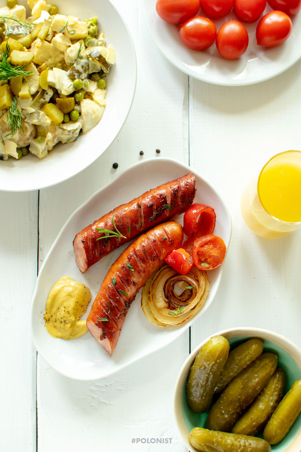 Grill Party table: Polish Grilled Kiełbasa Sausage on a white plate served with fried onions, cherry tomatoes and mustard. Dill pickles and Potato Salad. On a white wooden table, shot from above.