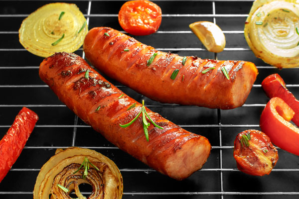 Polish Kiełbasa Sausage on a grill with onions, bell peppers, garlic and bell peppers. View from the side