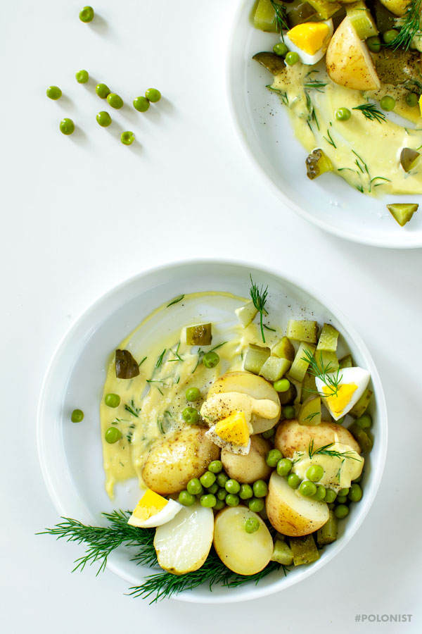 2 white plates with Polish Potato Salad, made with new potatoes, dill pickles, apple, onion, green peas and mayo. On a white background, shot from above.