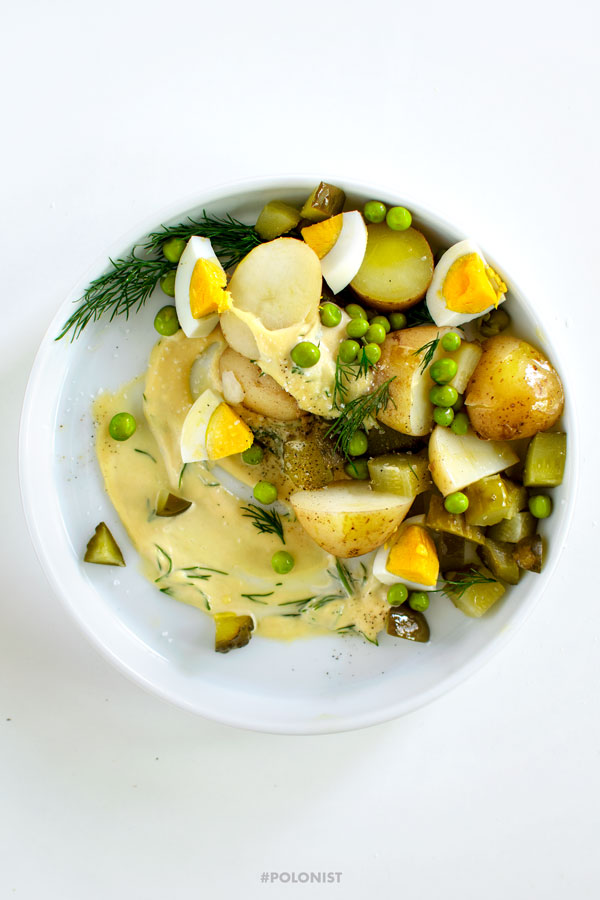 A white plate with Polish Potato Salad, made with new potatoes, dill pickles, apple, onion, green peas and mayo. On a white background, shot from above.