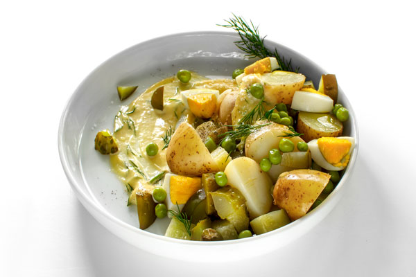 A white plate with Polish Potato Salad, made with new potatoes, dill pickles, apple, onion, green peas and mayo. On a white background, a side view.