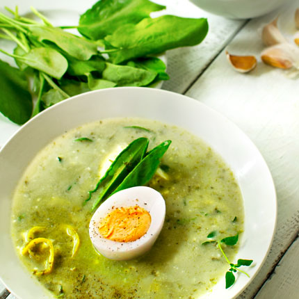 A plate of Polish Sorrel Soup, garnished with sorrel leaves and halved boiled egg, on a white, wooden table.