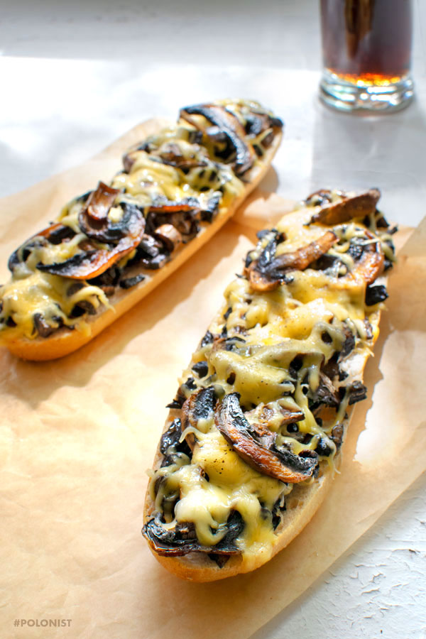 Polish fast food: 2 servings of zapiekanka: toasted baguette with fried mushrooms and melted cheese. Glass of soda in the background. On a white background.