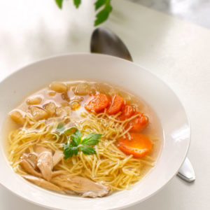Rosół: Polish Chicken Soup with thin egg Noodles. Served with sliced carrots, parsnip root and chicken meat. Served on a white plate, on a white table. Cutting board and lovage in the distance.