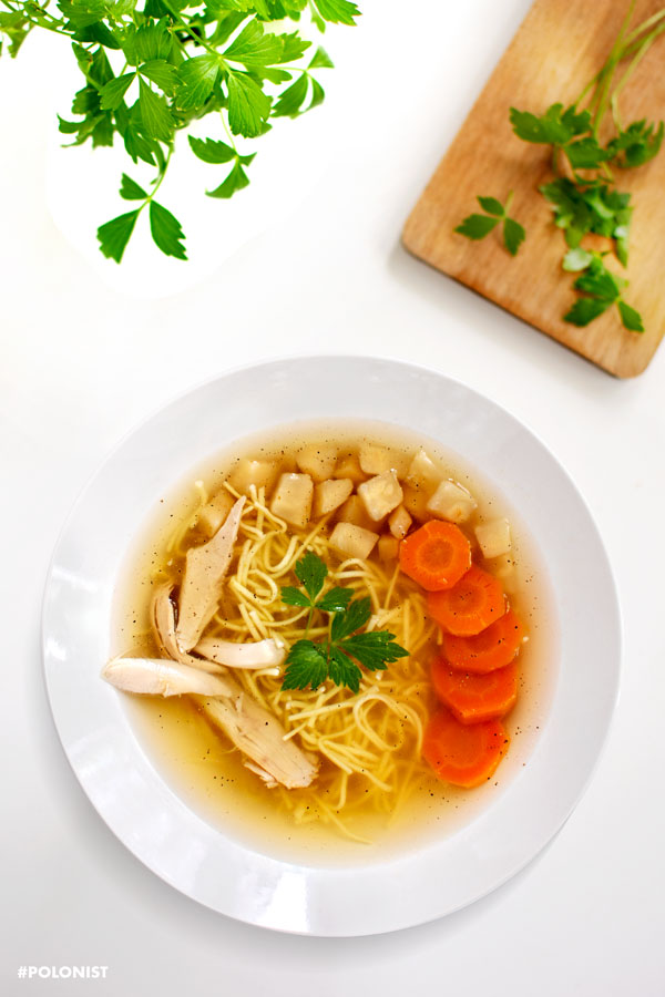 Top view of Rosół: Polish Chicken Soup with thin egg Noodles. Served with sliced carrots, parsnip root and chicken meat. Served on a white plate, on a white table. Cutting board and lovage leaves in the frame.