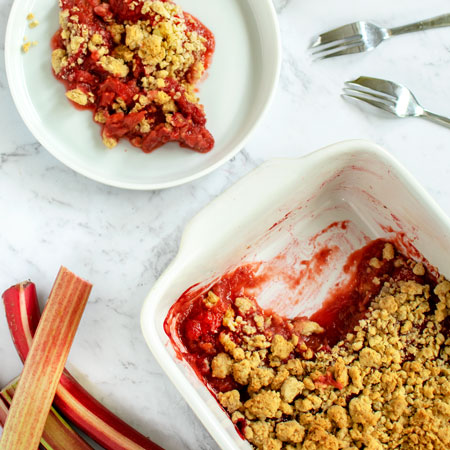 Strawberry Rhubarb Crumble with Oats in a baking dish with one serving on a white plate, on a white marble background - view from above/flat lay