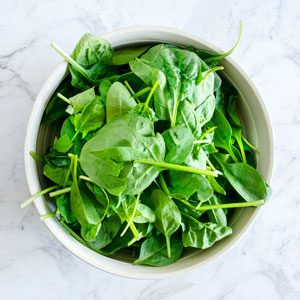 Top view of a bowl full of baby spinach leaves.