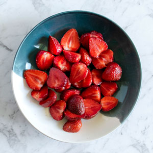 Top view of a bowl full of halved strawberries