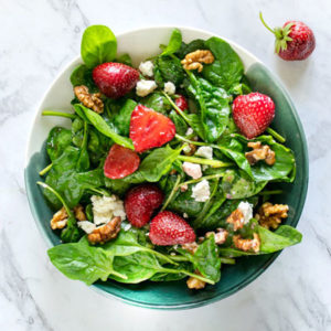Top view of a bowl with Baby Spinach Strawberry Walnut Salad with Goat Cheese. On a white marble background.