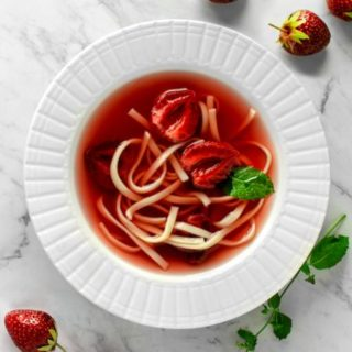Polish Strawberry Soup, Served with Egg noodles. Flat lay/ view from above, served on a white plate, on a white marble table.