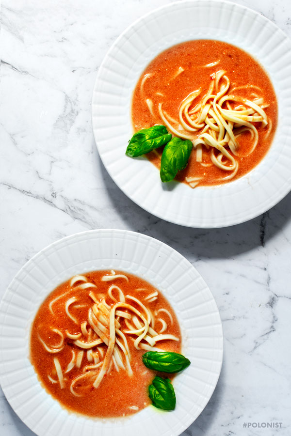 Flat lay of two white plates filled with Polish tomato Soup Pomidorowa, served with pasta, on a white marble background.