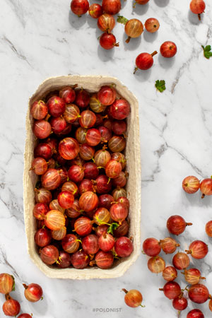 Flat lay of a paper basket filled with red gooseberries on a white marble background