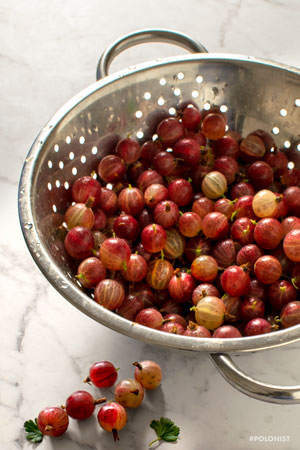 Silver Colander/strainer filled with red gooseberries