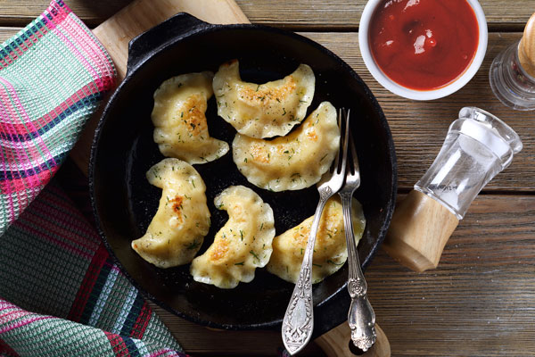 Pierogi served with ketchup sauce for dipping