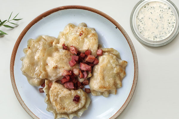 Pierogi sprinkled with fried bacon served with ranch sauce for dipping