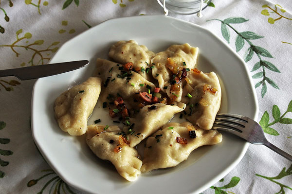 Pierogi in Butter, topped with chopped chives, fried onions and bacon