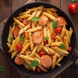 Kiełbasa sausage with pasta on a skillet