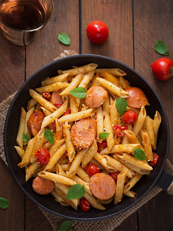 A skillet filled with pasta and kiełbasa sausage