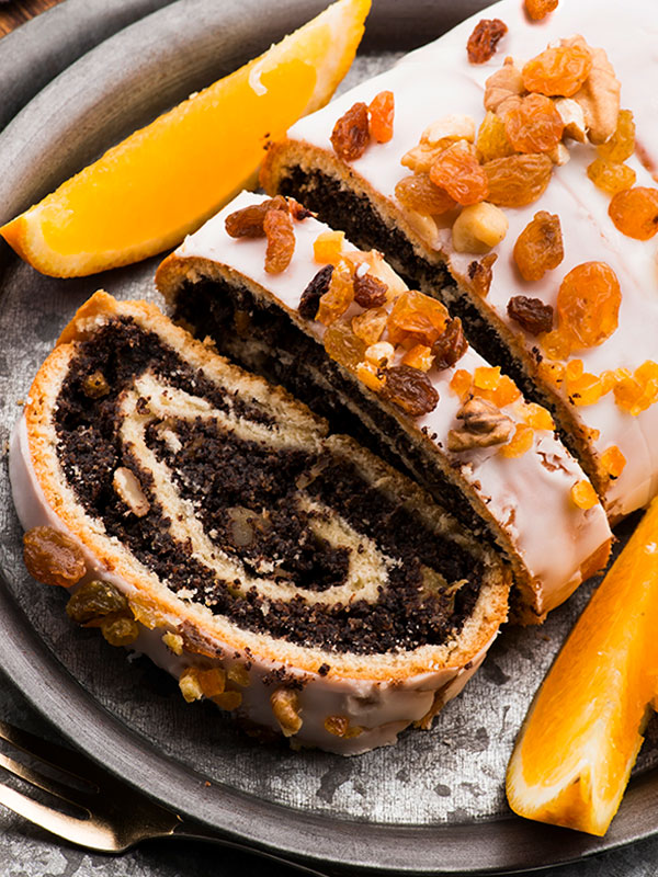 Poppy Seed Roll decorated with frosting, raisins and nuts.
