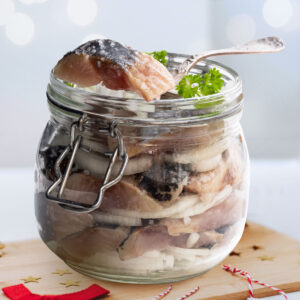 Pickled herring in vinegar with onions, in a jar