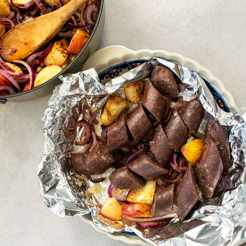 Blood sausage in oven dish, sitting on top of sautéed red onions and apples.