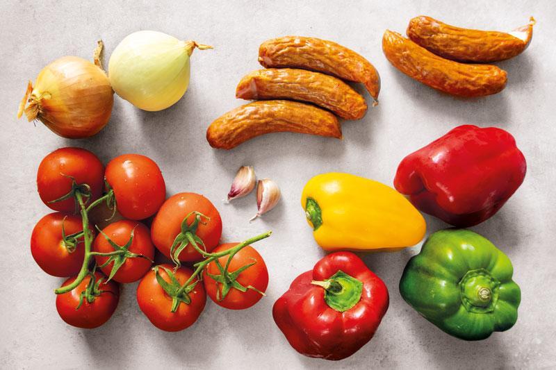 Ingredients for Polish Leczo stew: bell peppers, tomatoes, garlic, onions, kiełbasa sausage